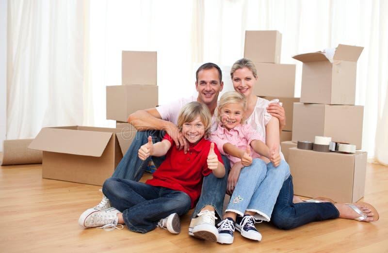 Assento de relaxamento da família alegre no assoalho fotos de stock