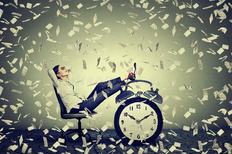 Assento de relaxamento da mulher de negócio em seu escritório sob a chuva do dinheiro imagens de stock royalty free