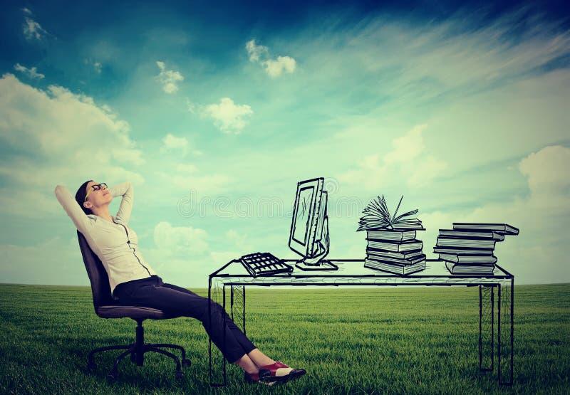Assento de relaxamento da mulher de negócios no escritório imagem de stock
