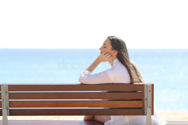 Assento de relaxamento da mulher em um banco na praia imagens de stock
