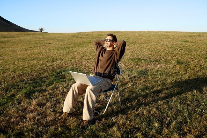 Assento de relaxamento do homem no campo com portátil fotos de stock