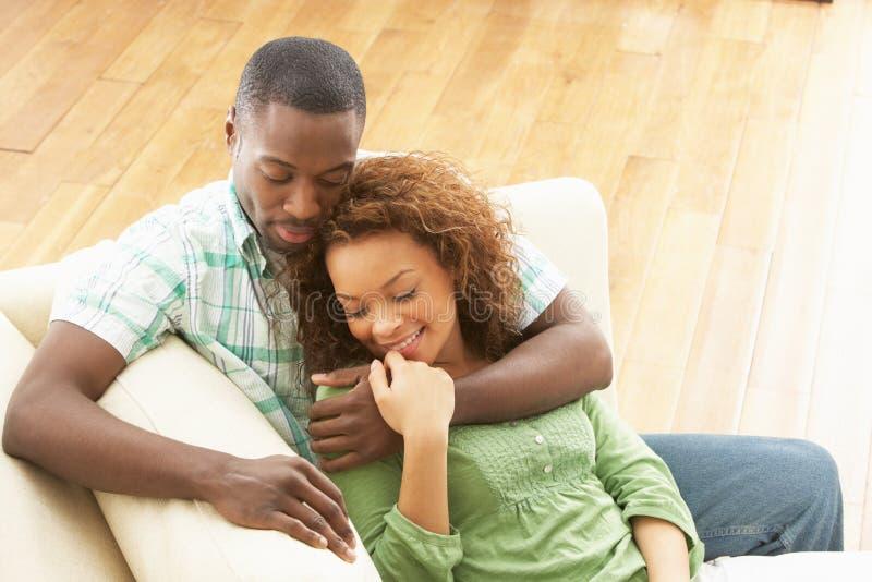 Assento de relaxamento dos pares novos românticos no sofá imagem de stock royalty free