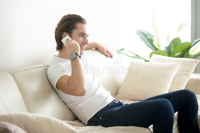 Assento de sorriso considerável novo do homem relaxado com telefone imagem de stock royalty free