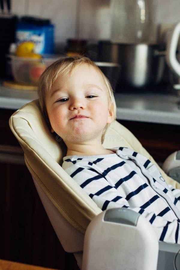 Assento de sorriso do infante louro engraçado pequeno em uma cadeira dos cuidados, olhando o imagens de stock