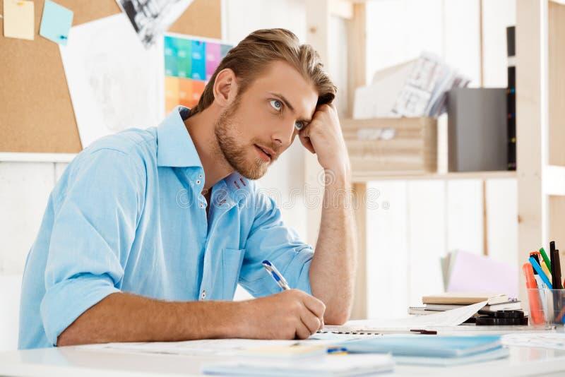 Assento de trabalho do homem de negócios pensativo seguro considerável novo na tabela que pensa sobre o bloco de notas Escritório fotografia de stock royalty free