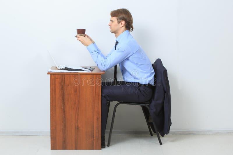 Assento do copo da posse do café ou do chá da bebida do homem de negócios fotos de stock