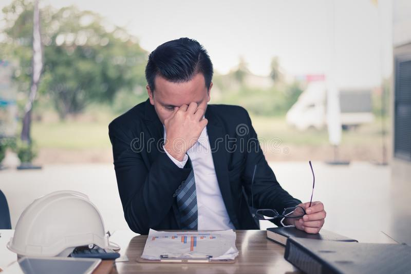 assento do homem de negócios e sua cabeça abraçada mão, é sentimento do forçado e tristeza da falha de negócio e do problema fina foto de stock