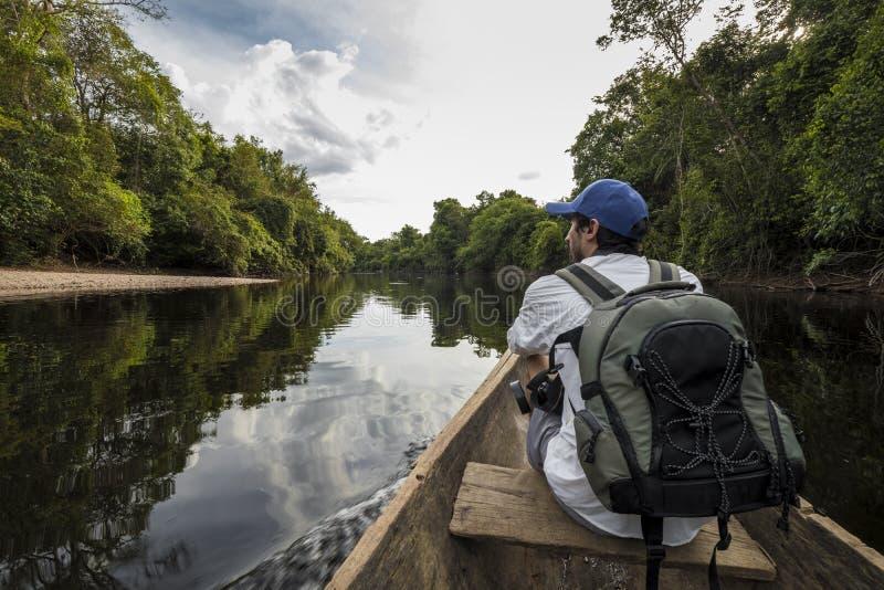 Assento do homem de Youg a bordo uma canoa na selva das Amazonas fotos de stock