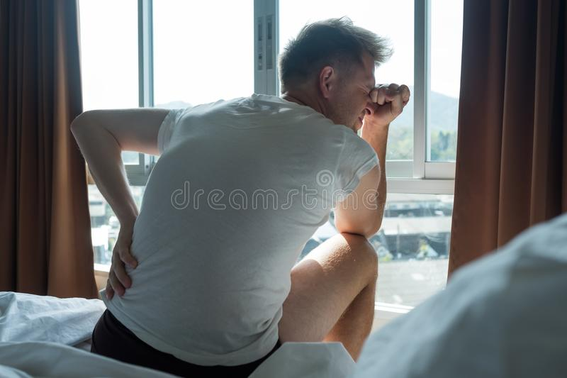 Assento do homem novo interno na dor do sentimento da cama no seu para trás imagem de stock royalty free