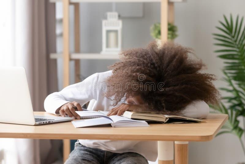 Assento do sono da estudante na mesa na sala de aula durante o estudo fotos de stock royalty free