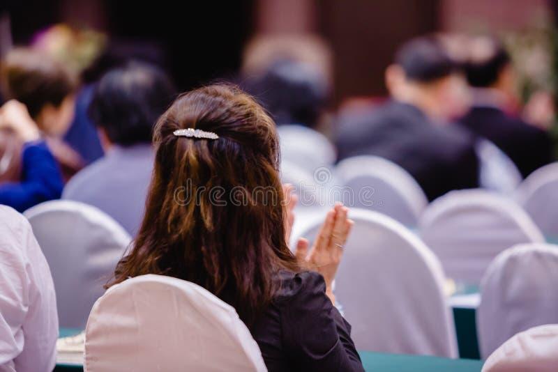 Assento e aplauso da mulher de negócio no auditório para reunião dos acionistas ' imagem de stock