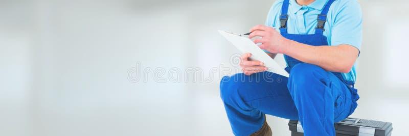 Assento e escrita do homem do encanador contra o fundo branco com alargamentos fotografia de stock royalty free