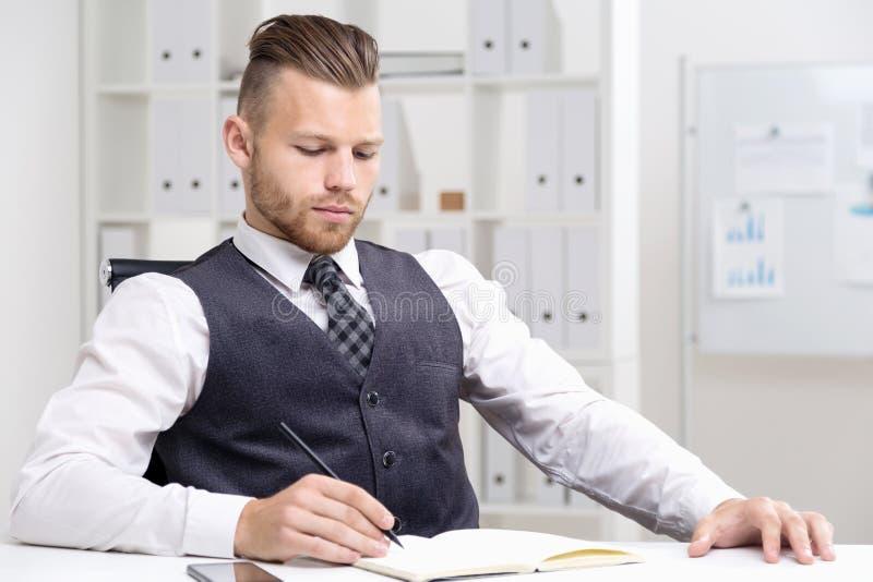 Assento e escrita novos do homem de negócios imagem de stock