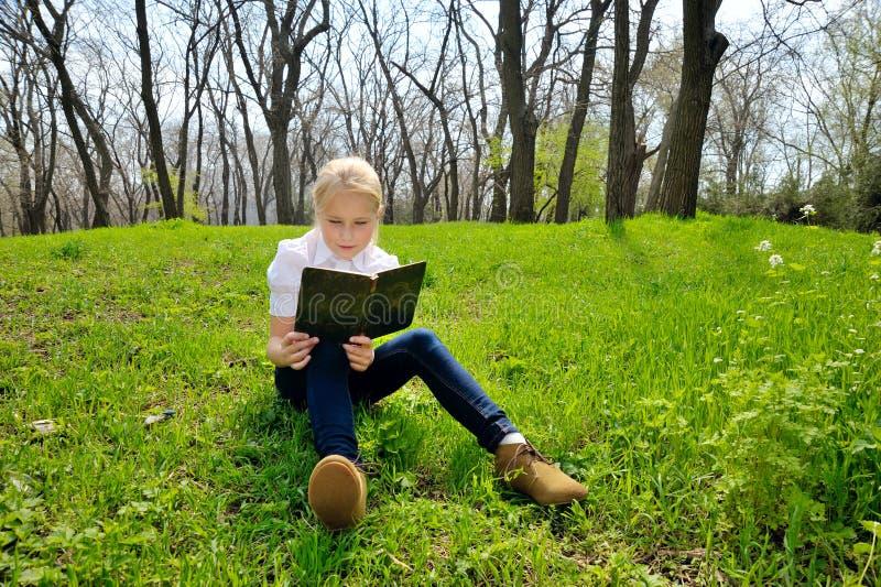 Assento e leitura da menina um livro na natureza foto de stock royalty free