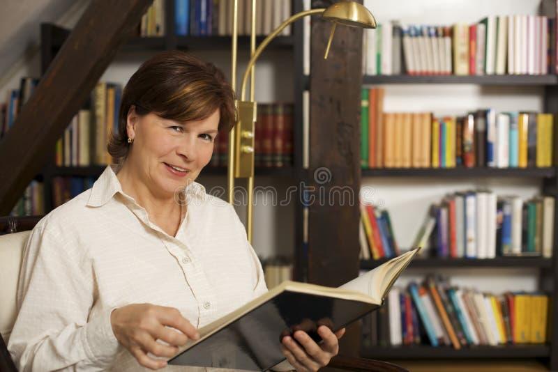 Assento e leitura sênior alegres da mulher um livro imagem de stock