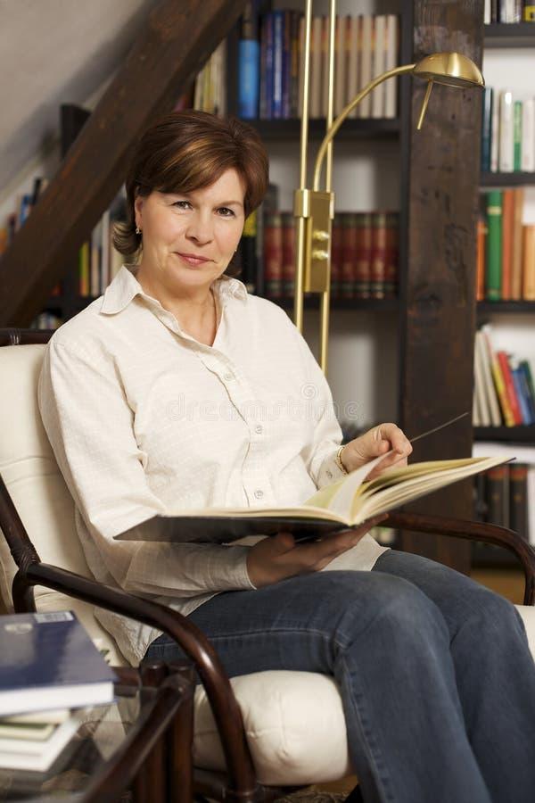 Assento e leitura sênior amigáveis da mulher um livro fotografia de stock royalty free