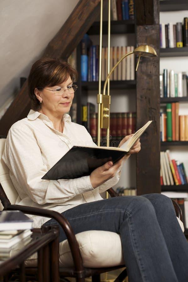 Assento e leitura sênior de sorriso da mulher um livro foto de stock royalty free