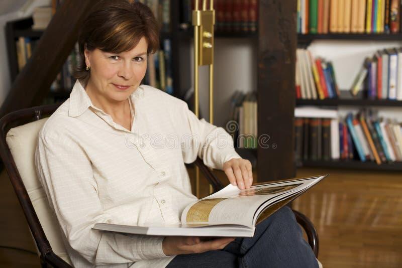 Assento e leitura sênior doces da mulher um livro fotografia de stock