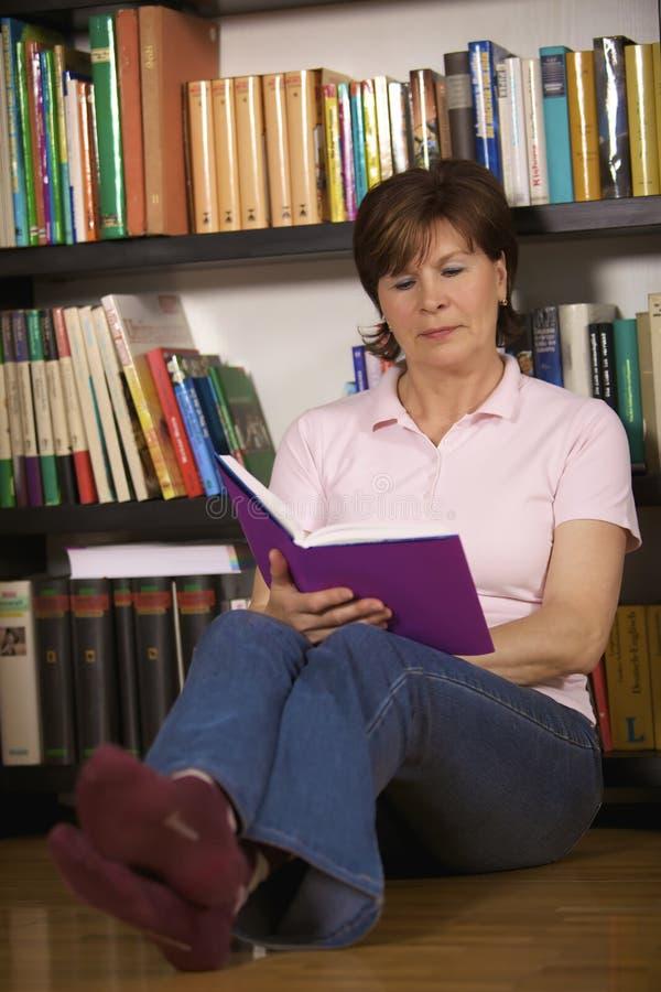 Assento e leitura sênior modernos da mulher imagem de stock