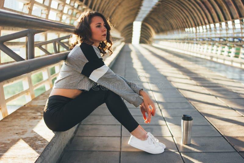 Assento e resto morenos novos atrativos da ginasta do dançarino da rua da mulher com o copo thermo na ponte da rua no nascer do s imagem de stock