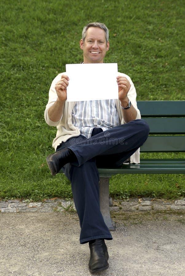 Assento e terra arrendada de Babyboomer um sinal em branco imagem de stock royalty free