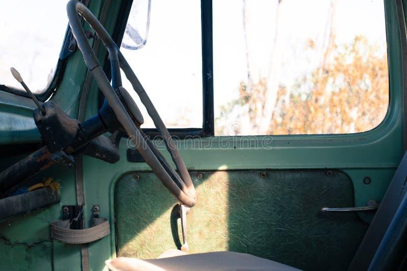 Assento e volante de motoristas em um caminhão verde velho oxidado foto de stock royalty free