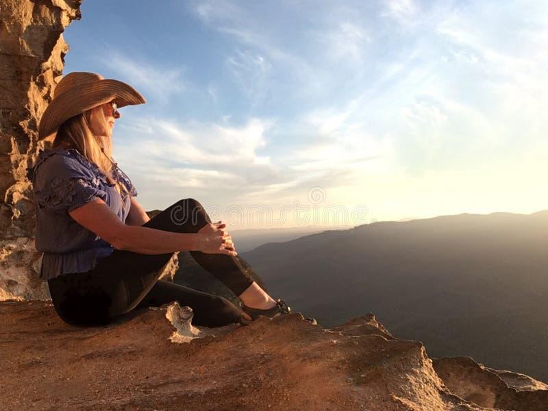 Assento em uma caverna da montanha que olha o sol ir para baixo fotos de stock