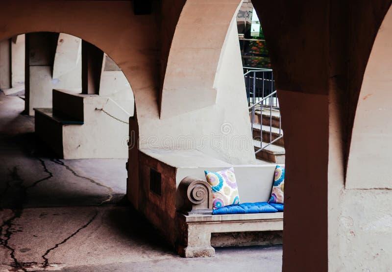 Assento exterior da rua com o coxim colorido sob a arcada do arco dentro foto de stock royalty free