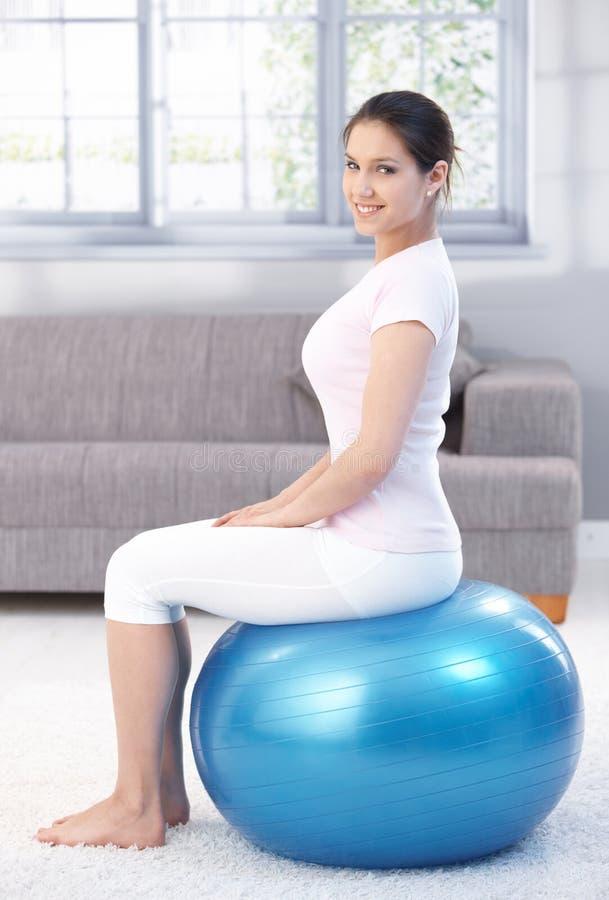 Assento fêmea atrativo na esfera do ajuste imagens de stock