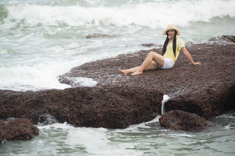 Assento fêmea bonito asiático em rochas com felicidade forte da onda e do abrandamento imagens de stock royalty free