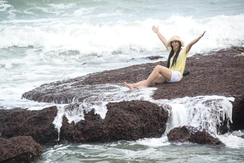 Assento fêmea bonito asiático em rochas com felicidade forte da onda e do abrandamento fotos de stock