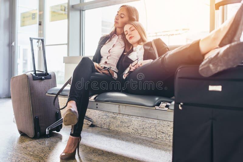 Assento fêmea cansado do sono de dois turistas no banco com bagagem perto deles na sala de espera no aeroporto fotos de stock royalty free