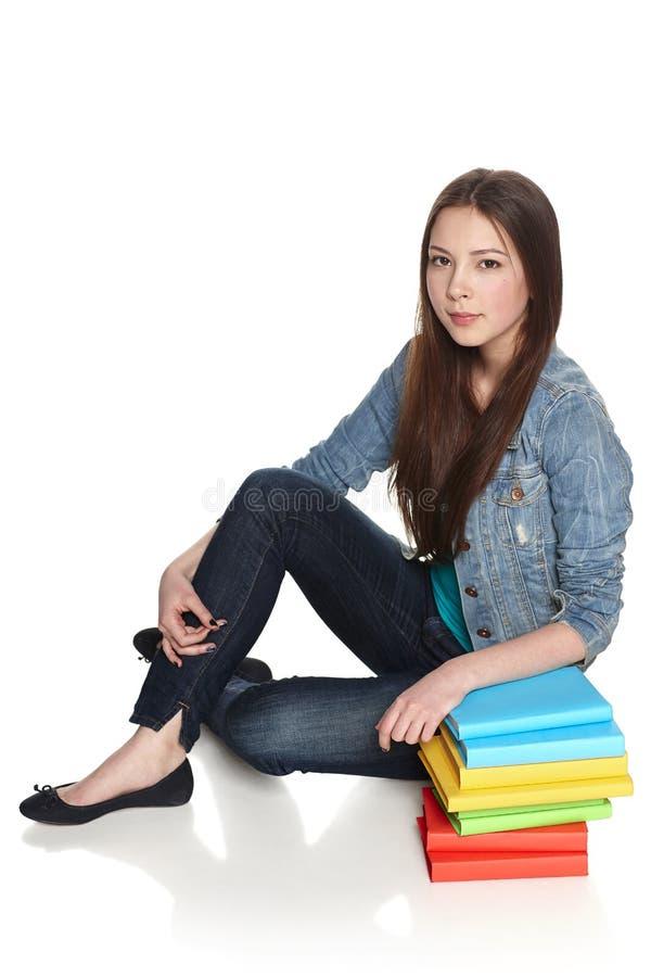 Assento fêmea com a pilha de livros foto de stock
