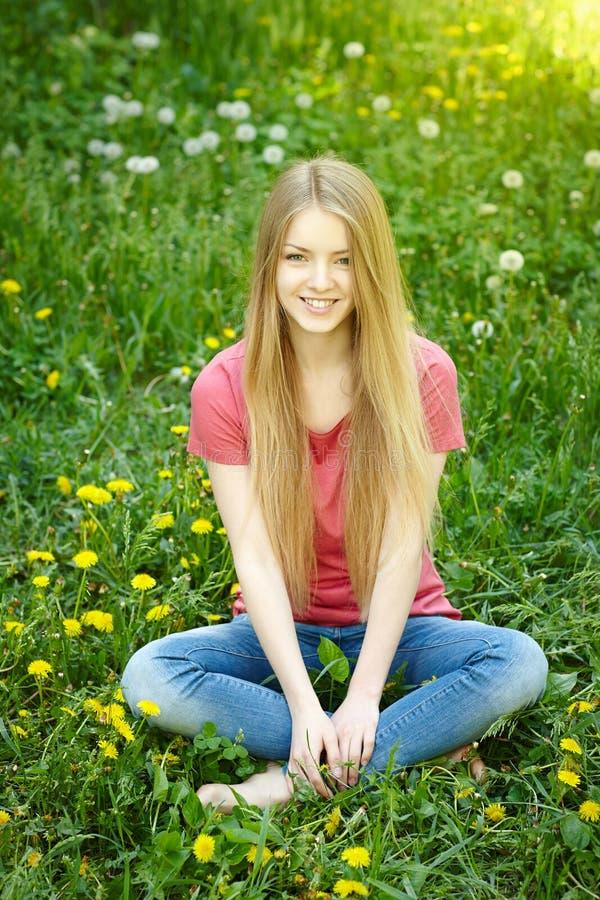 Assento fêmea de sorriso no campo dos dentes-de-leão imagem de stock