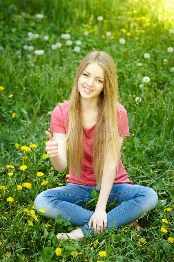 Assento fêmea de sorriso no campo dos dentes-de-leão fotos de stock
