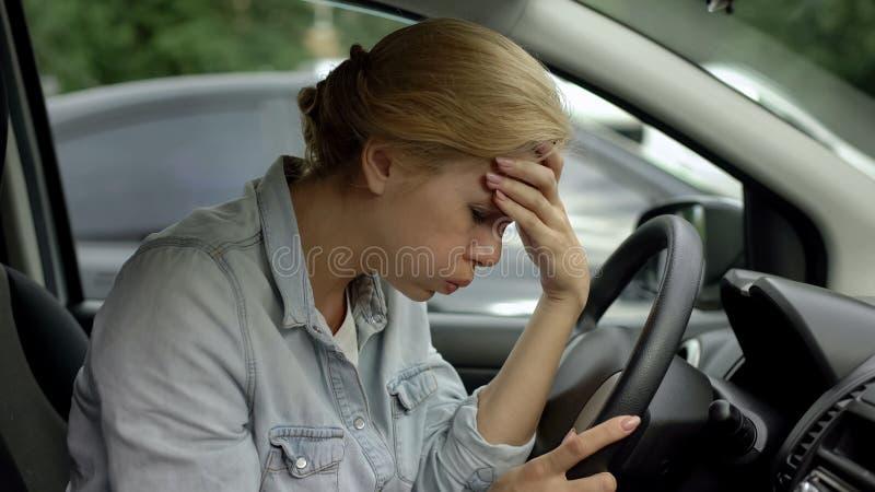 Assento fêmea louro no carro e dor de cabeça forte do sentimento, necessidade de analgésicos imagem de stock