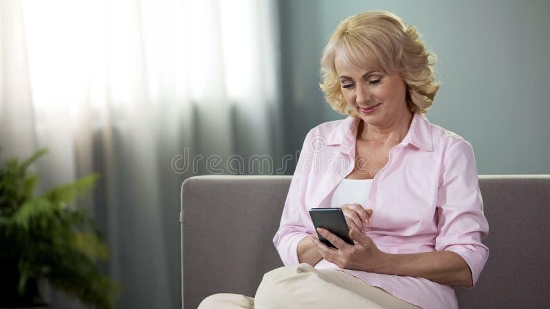 Assento fêmea maduro agradável em fotos do sofá e da filha da visão no smartphone fotografia de stock
