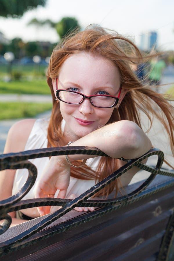Assento fêmea novo bonito no banco dentro fotografia de stock