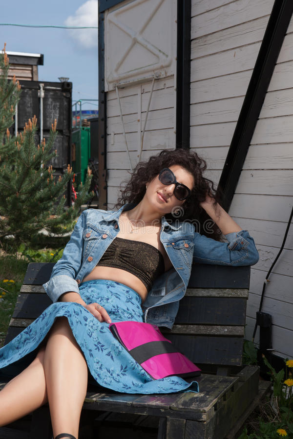 Assento fêmea novo no banco com óculos de sol fotos de stock royalty free