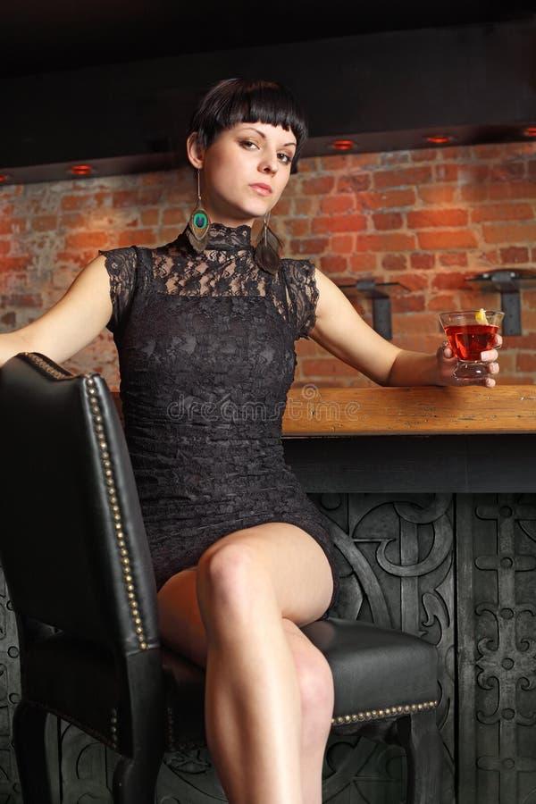 Assento fêmea 'sexy' em uma barra imagem de stock