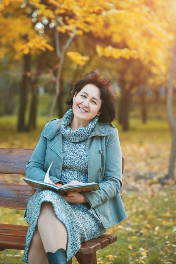 Assento fêmea superior no parque que aprecia um livro imagem de stock