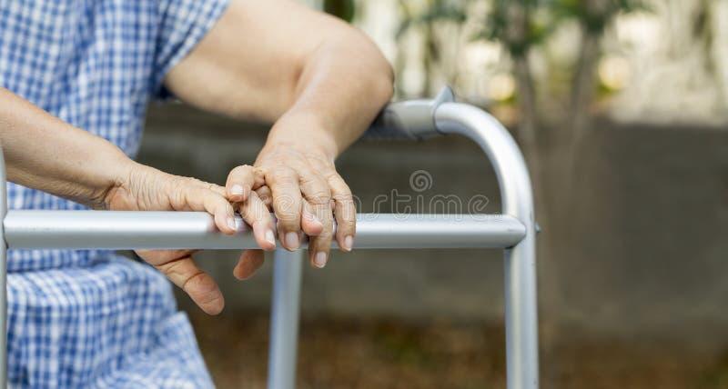Assento idoso no quintal com caminhante foto de stock