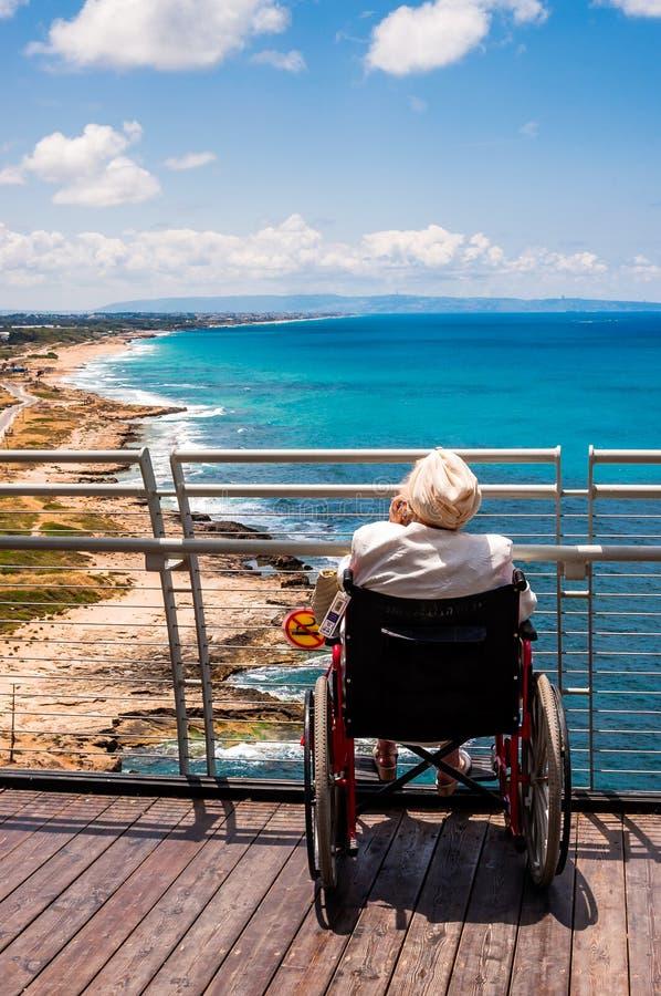 Assento inválido da mulher adulta na cadeira de rodas e no telefone celular de fala ao olhar à costa de mar Mediterrâneo norte de imagens de stock