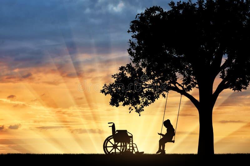 Assento inválido em um balanço sob uma árvore, leitura da estudante da menina um livro, ao lado de uma cadeira de rodas imagem de stock