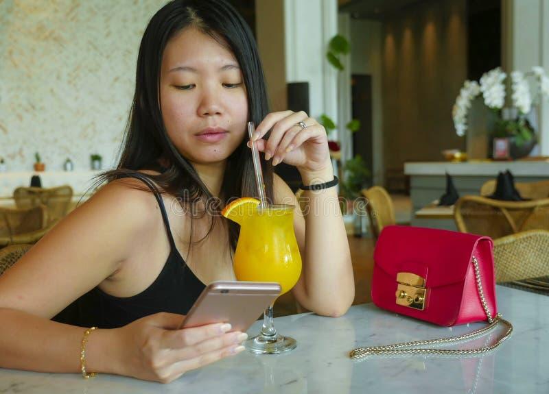 Assento japonês asiático bonito e feliz novo da mulher relaxado no restaurante da cafetaria ou do hotel usando o app social do  foto de stock