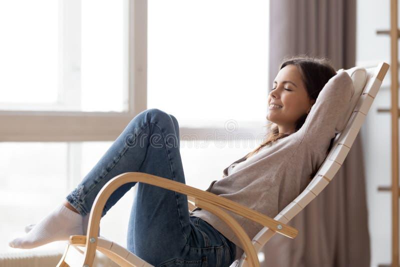 Assento lounging da jovem mulher calma relaxado na cadeira de balanço confortável imagens de stock royalty free