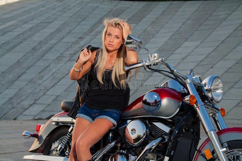 Assento louro 'sexy' em sua motocicleta fotos de stock royalty free