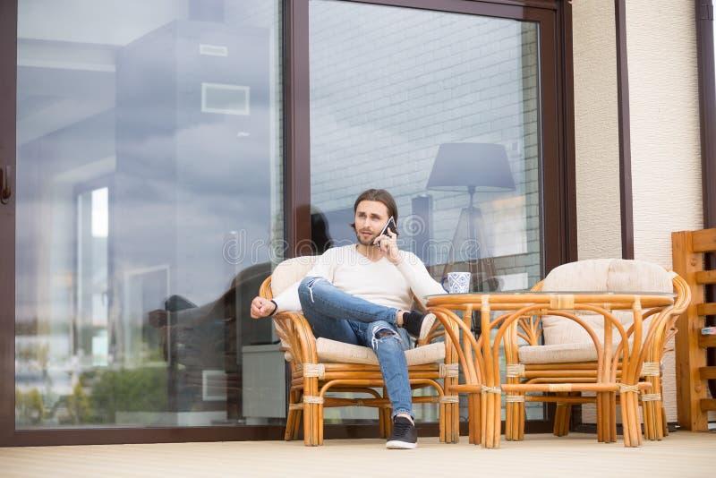 Assento masculino na poltrona do ar livre e fala pelo telefone imagens de stock