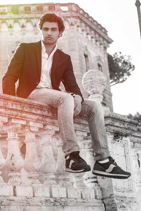 Assento modelo do homem à moda novo na parede velha do ponto baixo histórico Indicadores velhos bonitos em Roma (Italy) imagem de stock royalty free