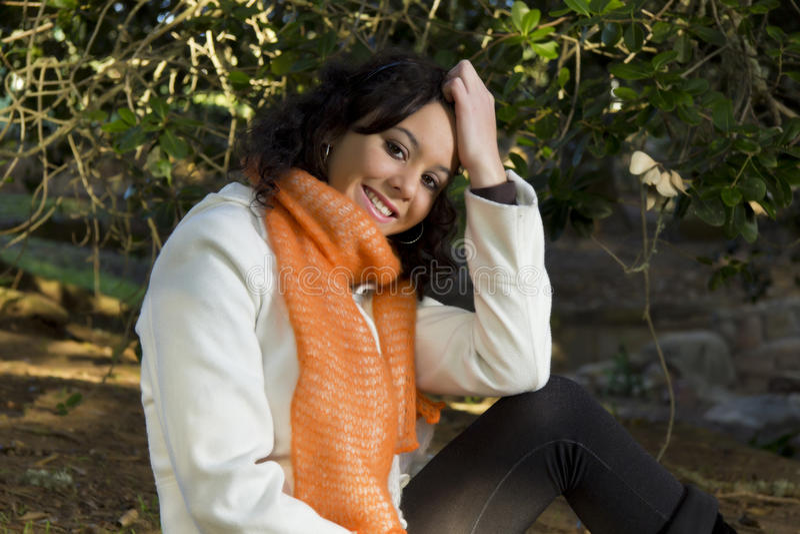 Assento modelo fêmea de sorriso feliz fora imagens de stock royalty free